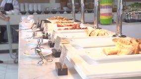 Tabla de buffet del desayuno en restaurante de lujo del hotel turístico con la comida clasificada de la panadería y los pastele metrajes