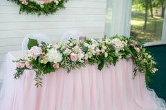 Tabla de cena blanca hermosa para los recienes casados adornados con verdor y el paño largo Centro de flores largo de las hortens fotografía de archivo