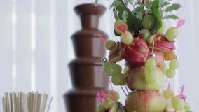 Tabla de comida fría con la fuente de la fruta, del champán, del jugo y del chocolate