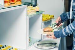 Tabla de comida fría del abastecimiento con la comida y los bocados para las huéspedes del evento Grupo de personas en todos lo q Foto de archivo libre de regalías