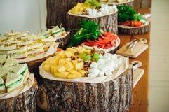 Tabla de comida fría exterior del abastecimiento con una comida deliciosa para las huéspedes del evento en estilo rústico Servici Imagenes de archivo