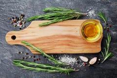 Tabla de cortar, aceite de oliva, planta del romero, sal, ajo y pimienta de madera en la tabla negra desde arriba para la comida  fotos de archivo libres de regalías