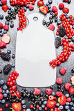 Tabla de cortar blanca y bayas frescas del verano en el fondo oscuro, visión superior fotografía de archivo libre de regalías