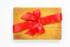 Tabla de cortar con la cinta y el arco rojos Fotografía de archivo libre de regalías