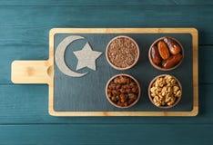 Tabla de cortar con la comida sana y la luna decorativa en fondo de madera fotografía de archivo