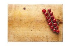 Tabla de cortar con los tomates de cereza Foto de archivo libre de regalías