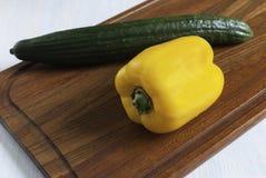 Tabla de cortar con pimienta amarilla y el pepino verde Foto de archivo