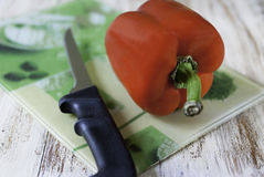 Tabla de cortar con pimienta y el cuchillo Fotos de archivo