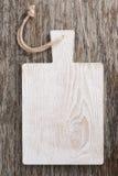 Tabla de cortar de madera ligera en un fondo oscuro, visión superior fotos de archivo libres de regalías