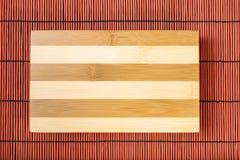 Tabla de cortar en la estera de bambú Imagen de archivo libre de regalías