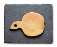 Tabla de cortar en una pizarra negra de la pizarra Fotografía de archivo