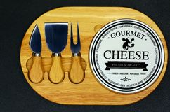 Tabla de cortar gastrónoma del queso con los cuchillos foto de archivo libre de regalías