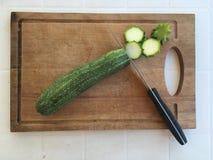 Tabla de cortar de madera con el calabacín cutted imagen de archivo