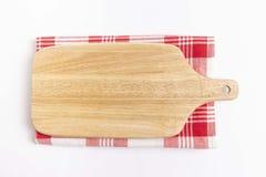 Tabla de cortar de madera en la materia textil a cuadros roja y el fondo blanco fotografía de archivo