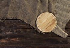 Tabla de cortar redonda en viejo fondo de madera oscuro fotos de archivo