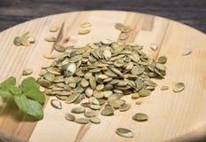 Tabla de cortar redonda de las semillas de calabaza y de las hojas de la albahaca Foto de archivo libre de regalías