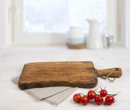 Tabla de cortar sobre mantel del lino en la tabla de madera Cocinar concepto foto de archivo
