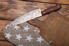 Tabla de cortar, tenedor de pote y cuchillo retros en viejo t quemado de madera Imagen de archivo