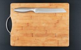 Tabla de cortar y cuchillo de la cocina en una tabla Fotos de archivo