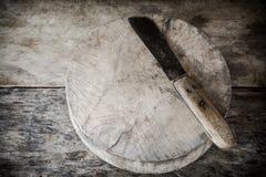 Tabla de cortar y cuchillo de madera viejos Fotografía de archivo