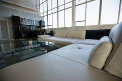 Tabla de cristal por el sofá blanco vacío en la oficina Imagen de archivo