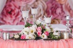 Tabla de la boda adornada con las flores frescas, las velas y las tazas de plata Fotos de archivo