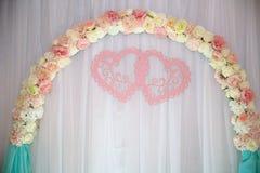 Tabla de la boda, arco del fondo adornado con las flores Imagen de archivo libre de regalías