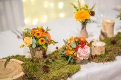 Tabla de la boda con el arreglo floral preparado para la pieza central de la recepci?n, de la boda, del cumplea?os o del aconteci imagen de archivo