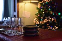 Tabla de la celebración de familia con los vidrios del champán y las placas apiladas en fondo del árbol de navidad imágenes de archivo libres de regalías