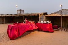 Tabla de la comida de la comida fría con la tela roja en el campo del desierto en Dubai imagenes de archivo