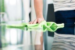Tabla de la limpieza del hombre en hogar con el paño Imagen de archivo libre de regalías