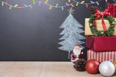 Tabla de la Navidad con las decoraciones y caja de regalo en el árbol de navidad Imágenes de archivo libres de regalías