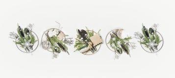 Tabla de la Navidad que fija endecha del plano Fila de placas con las ramas del abeto, los cubiertos y la decoración festiva del  fotografía de archivo libre de regalías