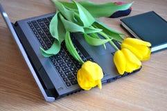 Tabla de la oficina con el ordenador portátil, el cuaderno y las flores Fotografía de archivo libre de regalías