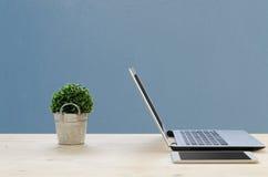 Tabla de la oficina con la pantalla de la libreta, árbol verde en cesta y noteb Fotos de archivo libres de regalías