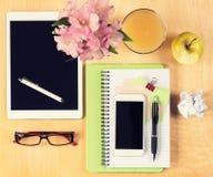 Tabla de la oficina con la tableta digital, el smartphone, los vidrios de lectura y la opinión sana del desayuno desde arriba Fotografía de archivo
