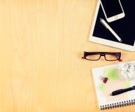Tabla de la oficina con la tableta, el smartphone, los vidrios de lectura y la libreta digitales Visión desde arriba Fotos de archivo libres de regalías