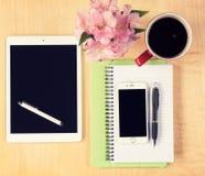 Tabla de la oficina con la tableta, el smartphone, los vidrios de lectura y la taza de café digitales Imagen de archivo