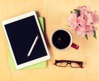 Tabla de la oficina con la tableta, los vidrios de lectura y la taza de café digitales Visión desde arriba Imagen de archivo