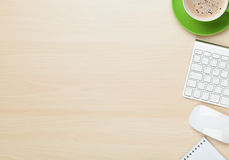 Tabla de la oficina con la taza de la libreta, del ordenador y de café
