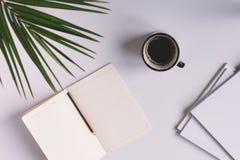Tabla de la oficina con la taza de la libreta y de café Visión desde arriba Imagen de archivo