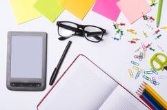 Tabla de la oficina con los accesorios: tableta, vidrios, cuaderno, pluma, p Imagen de archivo