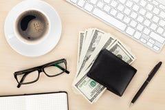 Tabla de la oficina con PC, las fuentes, la taza de café y el efectivo del dinero Fotos de archivo