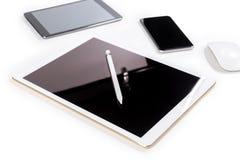 Tabla de la oficina con la tableta, el smartphone, el ratón y el lápiz digitales o Fotografía de archivo libre de regalías