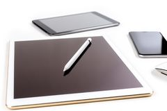 Tabla de la oficina con la tableta, el smartphone y el lápiz digitales en isola Imágenes de archivo libres de regalías
