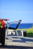 Tabla de la playa y sillas delante de la casa Fotografía de archivo