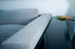 Tabla de la polvoreda del ama de casa cerca del sofá Imagen de archivo libre de regalías