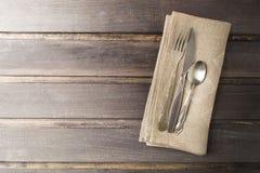 Tabla de la porción con estilo rústico y platos y cubiertos viejos en la tabla de madera foto de archivo