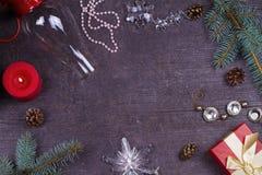 Tabla de la porción de la Navidad - placa, vidrio, lámpara, vela, conos del pino, caja de regalo Visión superior Fondo rústico co Fotografía de archivo
