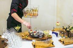 Tabla de la porción del camarero con delicioso y los aperitivos Servicio del abastecimiento Imagen de archivo libre de regalías
